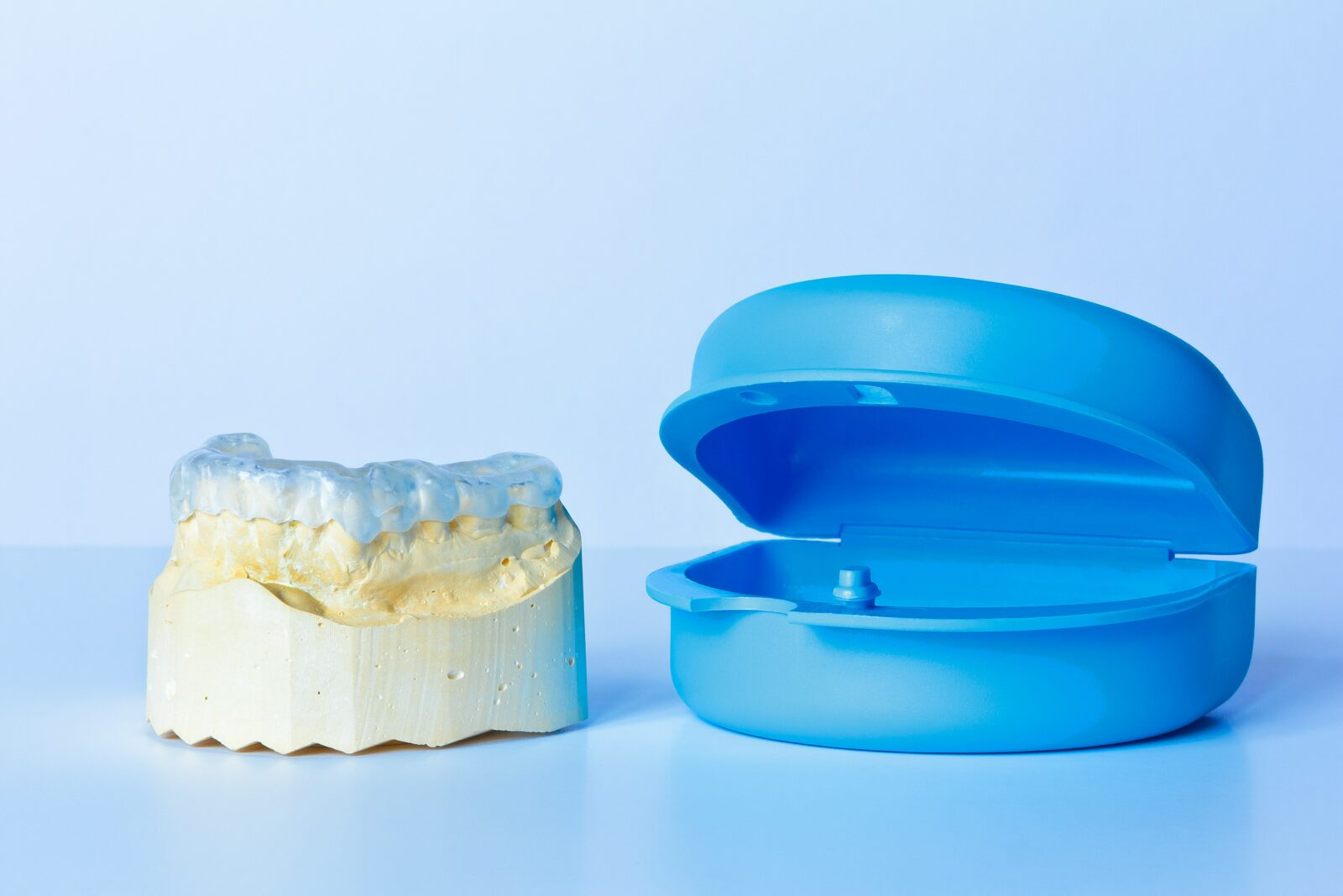 dental appliance on tooth model next to plastic case